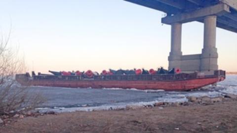 Капитан теплохода отбуксировал баржу к опорам Саратовского моста