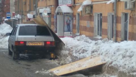 Рабочие накрыли листами фанеры машину, мешающую чистить крышу от снега