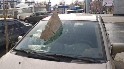 Кусок фасадной штукатурки пробил лобовое стекло машины