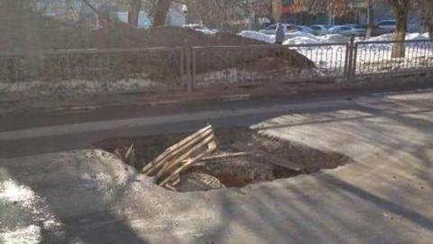 Огромная яма вокруг покосившегося люка появилась в центре Саратова
