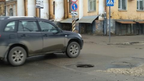 Открытый люк и незаконченный ремонт дороги сделали перекресток почти непроезжим