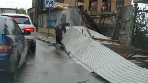 Порыв ветра снес забор от стройки на дорогу
