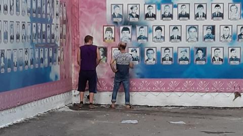 Двое мужчин справили нужду на плакат с портретами воинов-афганцев