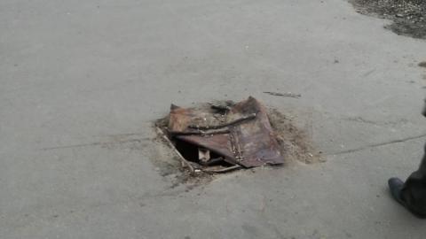 Открытый люк посреди тротуара прикрыли ржавым листом жести