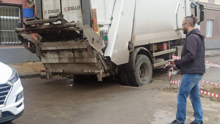 Мусовровоз застрял в яме коммунальщиков на Дзержинского